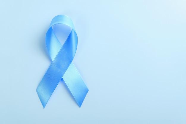青色の背景、前立腺癌意識の概念に青いリボン。