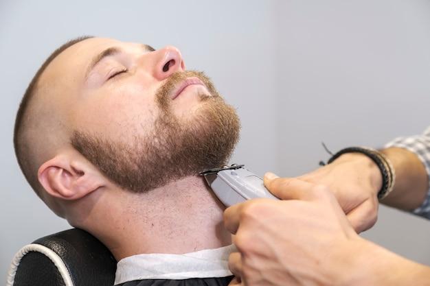 Парикмахер бреет бороду своего клиента с помощью электрического триммера.