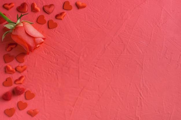 Праздничная композиция из красных роз и сердечек, разбросанных по розовому дню святого валентина