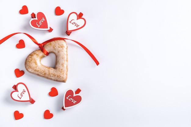 Печенье в форме сердца связано с красной лентой и разбросаны красные сердца на белом на день святого валентина