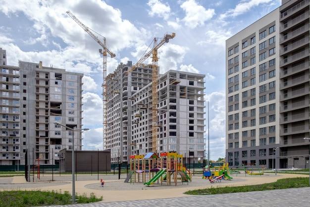 Многоэтажные дома, строительные краны, спортивная и детская игровая площадка в новостройке