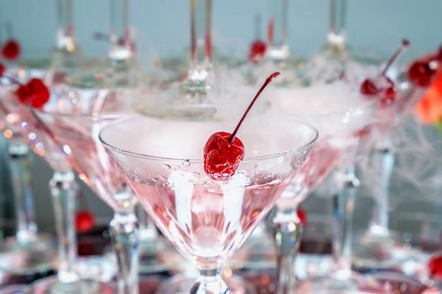 ピンクのアルコール飲料とグラスに赤いカクテルチェリー。