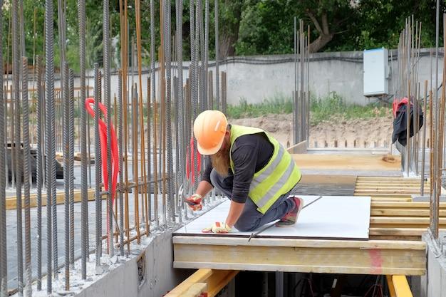 Бородатый рабочий на стройке собирает опалубку для заливки бетона