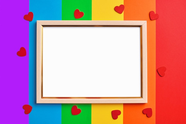 色とりどりの虹の旗の背景に空白の白いコピースペースを持つ木製フレーム