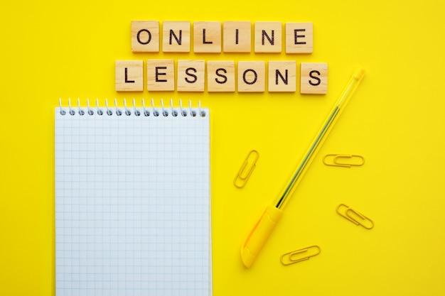 フレーズのオンラインレッスン、メモ帳、ペーパークリップ、黄色の背景にペンで木製レターキューブ。