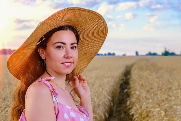 麦わら帽子の笑顔の若い長髪のウクライナの女性の肖像画