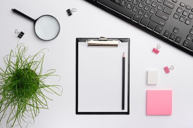 黒いキーボード、ステッカー、消しゴム、その他のオフィス用アクセサリを備えたホームオフィスデスクのワークスペース。