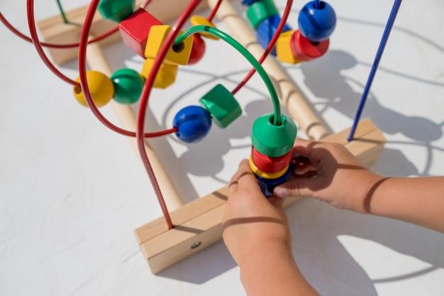 自宅で教育玩具で遊ぶ子供。子供向けのゲームを開発している小さな子供。カラフルなおもちゃを遊んで幸せな子。教育玩具。ゲームの開発、環境に優しい木製