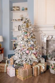 Интерьер гостиной с елкой и украшениями. красиво украшенный праздничный зал с елкой с подарками под ней. новогодний интерьер с елкой в белых, пастельных тонах