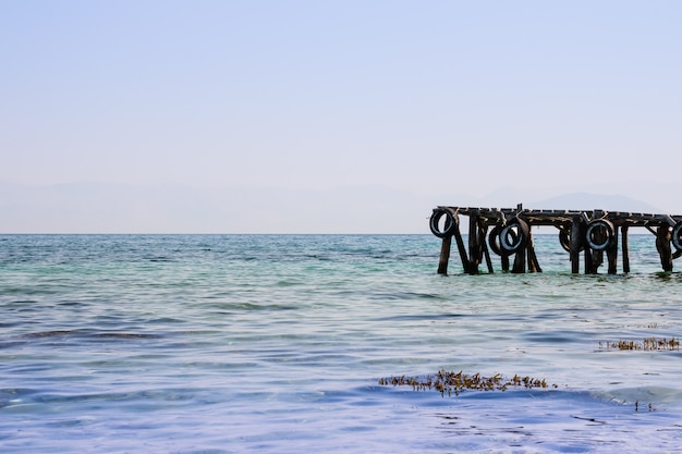 海の背景の自然海岸の美しいマリーナ。海の海岸線、澄んだ空に古い木製の桟橋。