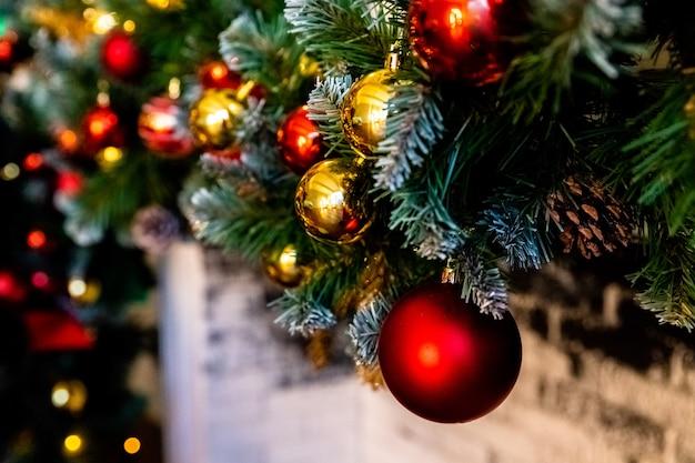 クリスマス暖炉、クリスマスライトデコレーション、木の枝。枝と弓の前景ボールで飾られたクリスマスツリー。暖炉のあるクラシックなアパートメント。クリスマスの夜。