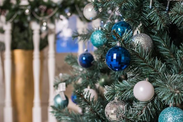 リビングルームで美しい照らされたクリスマスツリー。シックなクリスマスツリーで飾られた豪華なリビングルームのインテリア。青と銀のクリスマス飾り、ボール、見掛け倒し。