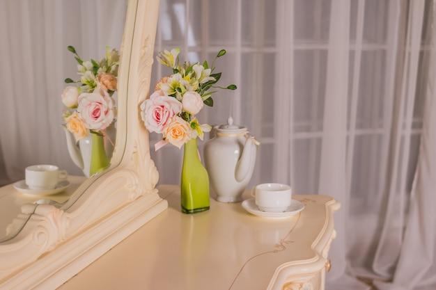 私室テーブル。女の子とメイクアップ、ミラー付きのヘアスタイルのための寝室のインテリア。ベッドでおはようコーヒー。私室のテーブル、ドレッシングテーブル。寝室のロマンチックなデザイン。