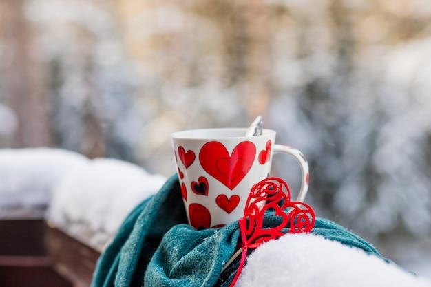 ホットチョコレートまたはコーヒー、カップの近くの赤いハート、焦点が合っていないライトと冬の背景。冬またはバレンタインデーの背景