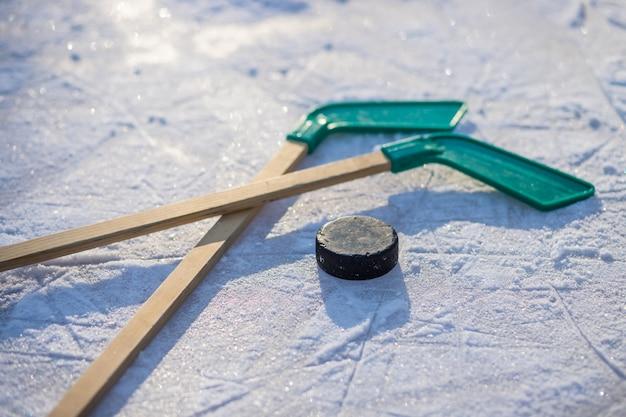 白いテープとパックのアイスホッケー用スティック。チームゲーム、ビジネスの競争概念。アイスホッケー用スティックとパック