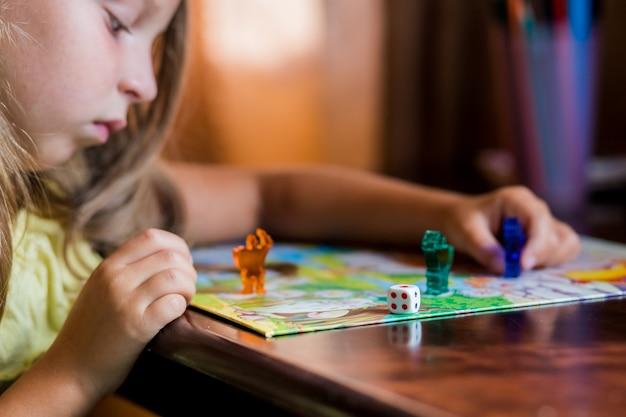 Маленькая блондинка держит фигуру в руке во время игры