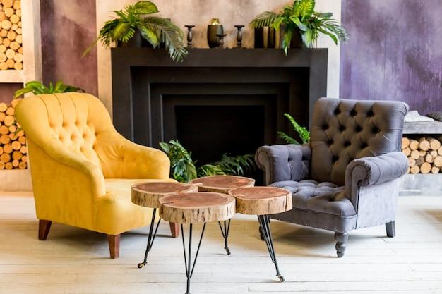モダンで豪華な家とリビングルーム、暖炉、アームチェア。カラフルな壁の装飾、木製の創造的なテーブル。暖炉のインテリアと居心地の良いインテリアルームスタイルのリビングルームコーナースタイル。