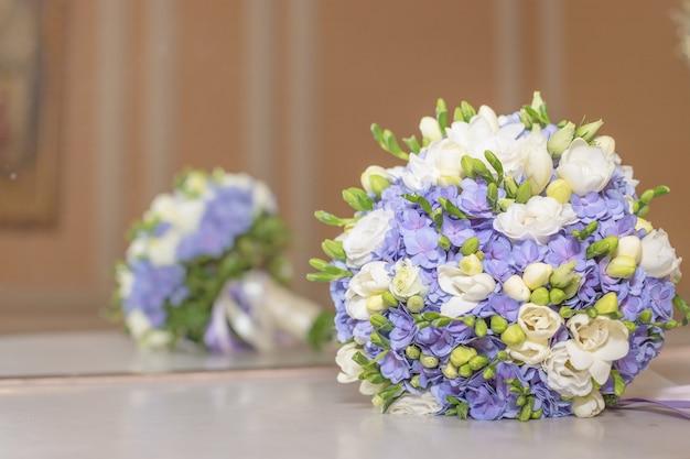 ウェディングブーケの花ブライダルブーケ。ミラーに対して大理石のテーブルに分離された美しい白青い花束。色とりどりの花の白と青のフリージアとアジサイ。コピースペース
