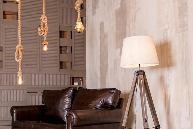 黄金色のランプ。大きな革のソファ。創造的なモダンなフロアランプ。レトロなエジソン電球がぶら下がっていて、ロフトの木製の天井に吊り下げられている。創造性のコンセプト。茶色のソファ。ロフトスタイルのアパートメント
