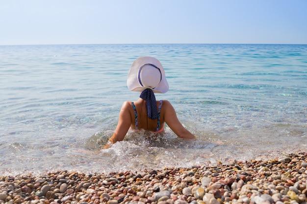 ビーチで小石にカメラに戻って座っている白い帽子の少女