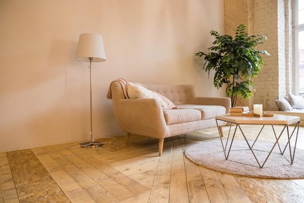 ロフトスタイルの部屋。ソファ、コーヒーテーブル、小さな木のインテリア。本とキャンドルのコーヒーテーブル付きソファ