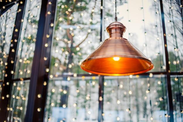 オレンジ色の光で明るい天井ランプの装飾家または店。