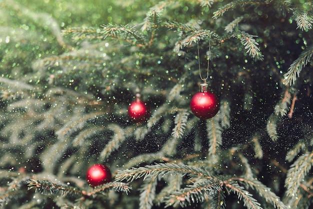 クリスマスツリーの安物の宝石。休日の概念。飾られたクリスマスツリーからぶら下がっている赤い安物の宝石。