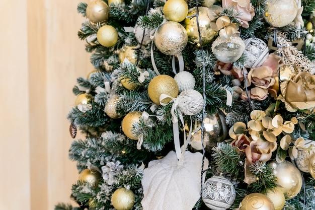光沢のあるまぶしさでクリスマスツリーに掛かっている美しい色のクリスマスの装飾。新年の家の装飾、ゴールデンボール、ガーランド、つまらないもの、伝統的なお祝いで飾られたお祝いツリー