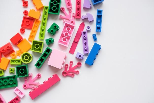 色とりどりのプラスチック製ビルディングブロック。おもちゃの明るい小さなスペアパーツの部品。