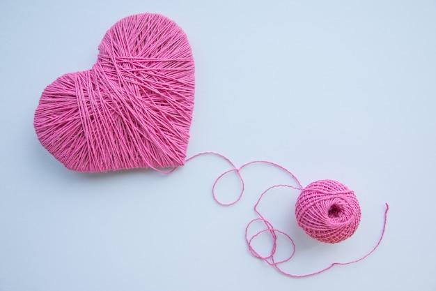 白で隔離されるカラフルな糸玉。愛の象徴のようなピンクのハート。趣味のコンセプト。イベントのはがき