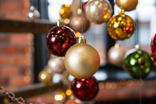 Цветной рождественский шар висит на струнах. праздничный фон открытки на новый год, креативные елки. установить рождественские безделушки. идеи для современного оформления, ресторан, отель, зимняя свадьба