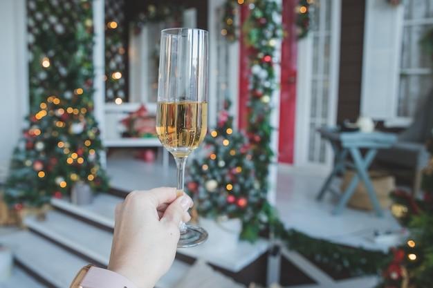 Тост с бокалом шампанского в женской руке. празднование в канун нового года. концепция вечеринки, напитки, праздники, люди и торжества. украшение шампанского и нового года. партия с игристым вином