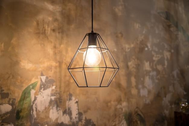 暗闇の中でガラスの電球の中に輝くフィラメントを備えた工業スタイルのワイヤーランプ。光沢のあるライトと暗い背景。ケージランプシェードと都市スタイルのインテリア照明。グランジ装飾。