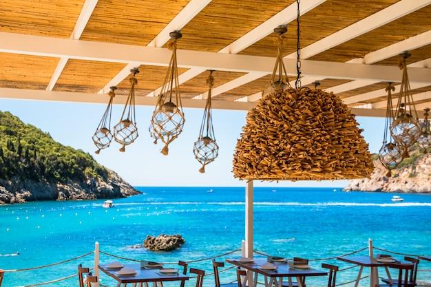 大きなガラス玉と海辺のカフェの外の行の電球。カフェからの最大の眺め。オープンレストランのリラックスしたインテリア。コピースペース