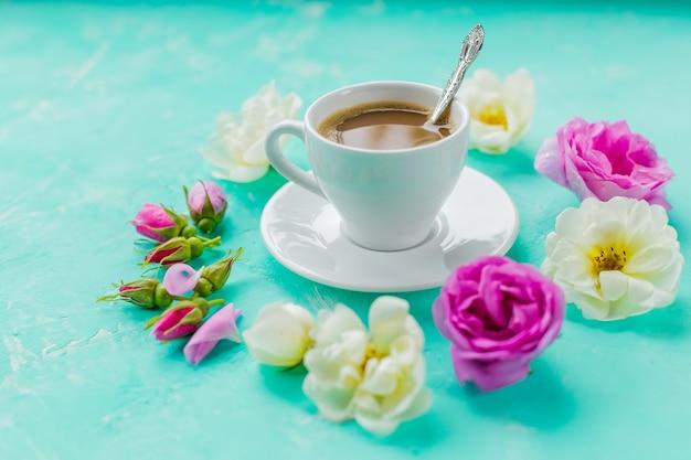 Утренняя чашка кофе и свежие красивые розовые и белые розы цветы, плоский макет, копия пространства. концепция кофейного напитка с чашкой американо и розы на бетонном фоне. утренний женский фон