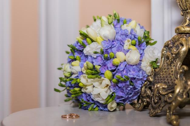 Обручальные кольца лежат и красивый букет, как свадебные аксессуары. два золотых кольца и свадебные цветы. поздравительная открытка, приглашение, красочные цветы белые и синие фрезии и гортензии. копировать пространство