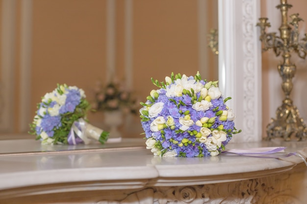 大理石の背景にフリージアとラナンキュラスの単にエレガントなブーケ。白い大理石のテーブル、黄金のシャンデリアに白と紫のアジサイの花。繊細な花嫁のブーケ