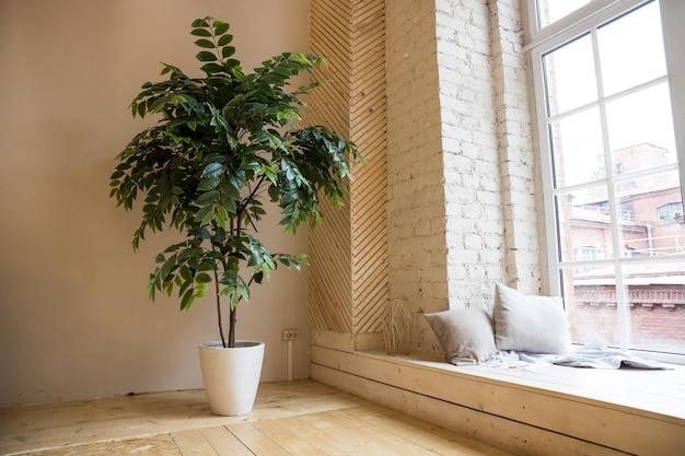 最小限のデザイン。中庭を見下ろす大きな窓のあるロフトルームアパートの部屋の明るいインテリア。家と庭のコンセプト。