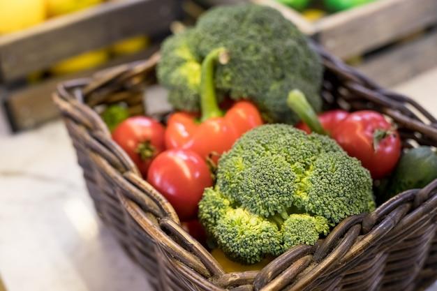 テーブルの上のバスケットで新鮮な野菜。赤いトマト、ブロッコリー、ジャガイモ、ピーマン、赤いパプリカ。バイオ健康食品、ハーブ、スパイス。有機野菜。セレクティブフォーカス。