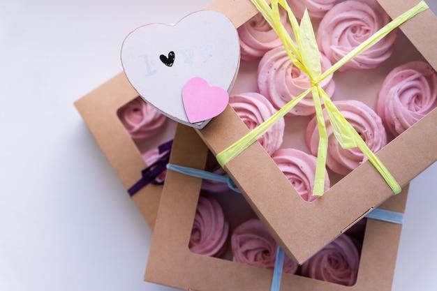 プレゼントボックスに自家製のピンクのゼファーまたはマシュマロをクローズアップ。マシュマロ、メレンゲ、ゼファー。バレンタインや母の日のコンセプト。心の贈り物。愛と感情。