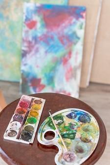 Художественное оборудование в мастерской, мольберт, кисти, тюбики с краской, палитра и картины на работе художника, таблица. раскраска картины на холсте.арт школы