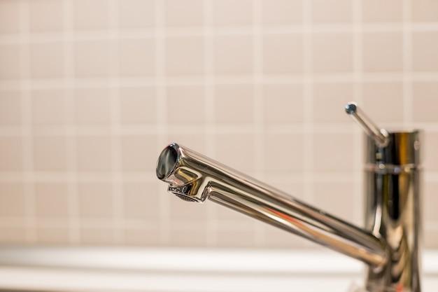 台所の流しおよび現代ステンレス鋼の台所水蛇口のコック。
