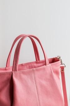 白い壁に分離されたエレガントで豪華なファッションレザーピンク女性ハンドバッグ