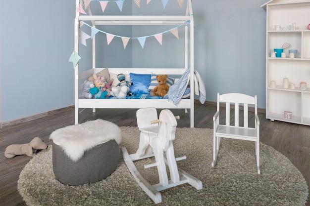 Стильная мебель в однотонной просторной детской комнате. современный интерьер спальни с маленькой украшенной детской кроваткой. традиционная лошадка-качалка