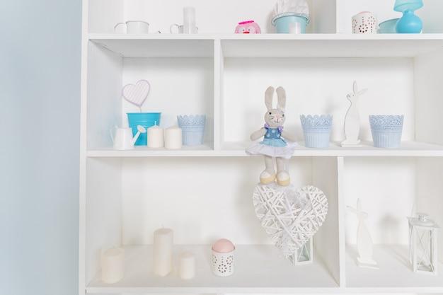 Книжный шкаф с пасхальными игрушками, свечами, вазами. полочки с мягкими игрушками кроликов в оформлении детской комнаты. кролики-кролики.