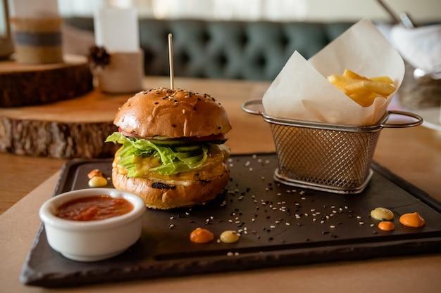 Вкусные гамбургеры с картофелем фри. сэндвич - популярный фаст-фуд на бранч