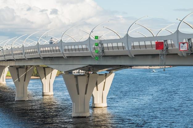 曇り空に対して主要な完全な川に架かる大きな橋。アーバンビュー。チャンネルをブリッジします。海の上の高架橋。