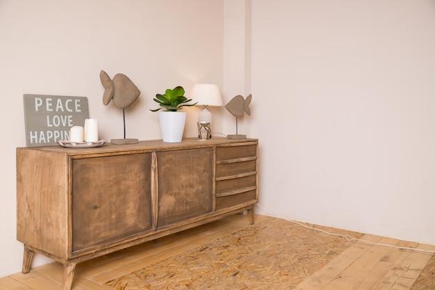 白いキャンドル、ランプ、小さな鉢植えのある居心地の良い部屋が胸に置かれています