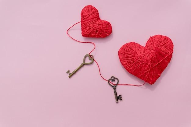 День святого валентина концепция, ключ и красные сердца, изолированные на розовом фоне.