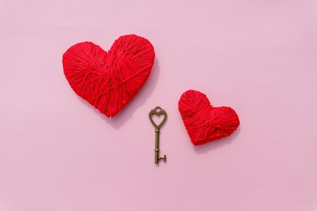 Счастливый день святого валентина фон с двумя сердцами на розовом фоне. красный и розовый символ формы сердца из шерсти. старинный ключ и красное сердце.